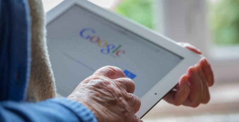 Kuva tablettia käyttävästä ihmisestä